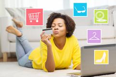 happy african woman with laptop and credit card - stock photo