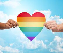 human hands with rainbow heart shape over blue sky - stock photo