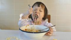 Little girl eating noodle by herself Stock Footage