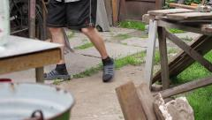Old man walking on the yard. Rural grandfather. Legs of old man. Stock Footage