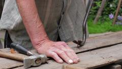 Old carpenter repairing the box. Old man takes out the nails. Stock Footage