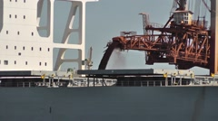 Crane loading freight ship with iron ore Stock Footage