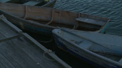 Two old, wooden rowboats tied to a dock. - stock footage