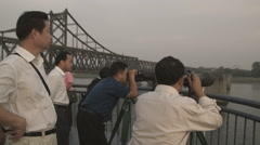 Men viewing North Korea from China. Stock Footage
