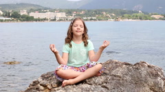 Little girl sitting on a rock by the sea and meditates Stock Footage