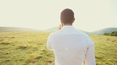 Young business man talking on cell phone at nature. Stock Footage