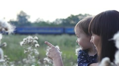 Mom and little daughter on nature have fun watch train pass by Stock Footage