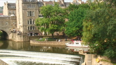 Pulteney Weir and bridge with a ferry on the River Avon in England. Stock Footage