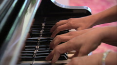 Multiple hands playing the piano. Stock Footage