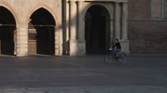 Man riding a bicycle in a plaza in Bologna Italy. Stock Footage