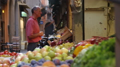 Man and fruit at a market in an alleyway in Bologna Italy. - stock footage