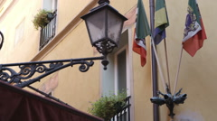 Street light and flags by a building in Bologna Italy. Stock Footage