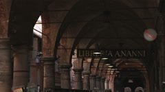 Tilt from arches in a walkway to people in Bologna Italy. Stock Footage