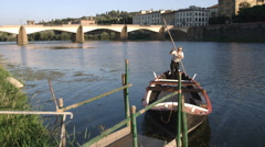Man pulling into a river dock in a gondola in Italy. Stock Footage