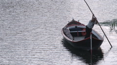 Man in a gondola pushing off shore into a canal in Italy. Stock Footage
