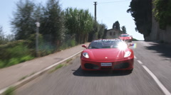Two Ferraris driving down an Italian country road. Stock Footage