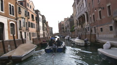 Motorboat passing by buildings on a canal in Venice. Stock Footage