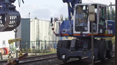 Crain machine lifting a piece of railroad track - stock footage