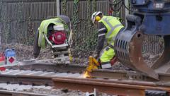 Railroad track working operating buzz saw with sparks Stock Footage