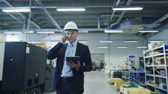 Businessman on the Phone Walking through Factory Stock Footage