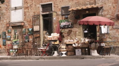 Girl walking past a store in a village in Tuscany Italy. Stock Footage