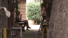 People conversing in an alleyway in a village in Tuscany Italy. Stock Footage