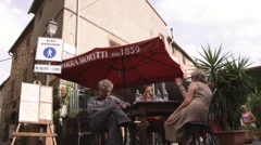 People conversing in a cafe in a Tuscan village in Italy. Stock Footage