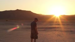 A man watching the sunset in the desert Stock Footage