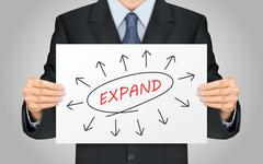 businessman holding expand word poster - stock illustration