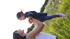 Mom throw little child daughter up in air on nature sunset light haze - stock footage