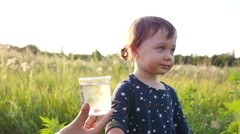 Mother gives child daughter drink clean pure water but she refuses - stock footage