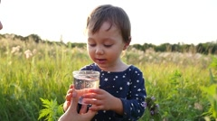 Mother gives child daughter drink clean pure water on sunset nature - stock footage