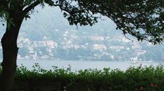 Tree silhouette with Lake Como and villa in background in Italy. - stock footage
