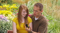 Young man proposing to a young woman in a beautiful garden. - stock footage