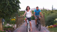 Young couple riding bikes through a beautiful garden. - stock footage