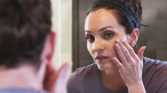 Close-up of a mirror as a woman applies face cream. - stock footage