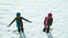 Twin girls fall back into a snow drift. Stock Footage