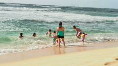 Mother watching children playing in the waves in Hawaii. - stock footage
