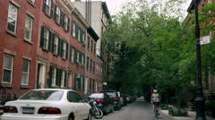 Woman on Citi Bike bicycle, riding down quiet street in West Village, 4K, NYC Stock Footage