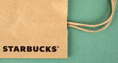 Starbucks paper bag on green background Stock Photos