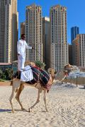 Man riding a camel on the beach Stock Photos