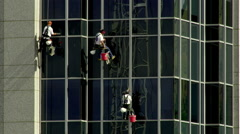 Stock Video Footage of Men rappelling and washing windows at a construction site in SLC Utah.