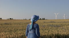 A woman in a blue dress walks through a wheat field with wind turbines. Stock Footage