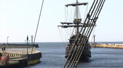 Old caravel sailing ship enters a port. Shot from another historic ship. Stock Footage