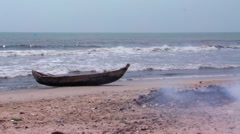 Boat on a beach in Africa with a fire in the foreground. Stock Footage
