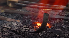 Metal tools lying next to a small fire Stock Footage