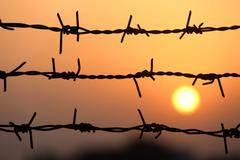 Setting sun behind barbed wire Stock Photos