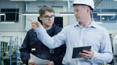 Engineer in Hard Hat and Factory Worker are Walking through Production Facility Stock Footage