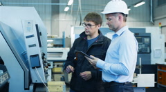 Engineer and Factory Worker are Setting Up CNC Lathe Machine on Factory Stock Footage