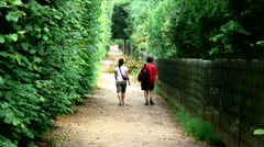 Man and woman walking down a trail through greenery in Paris, France. Stock Footage